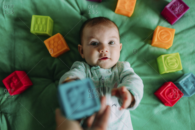 Portrait of baby girl lying on green mat playing with rubber toys