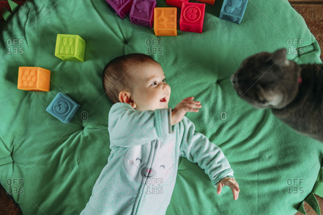 Happy baby girl lying on green mat watching cat