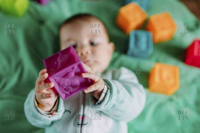 Baby's hands holding purple rubber cube toy- close-up