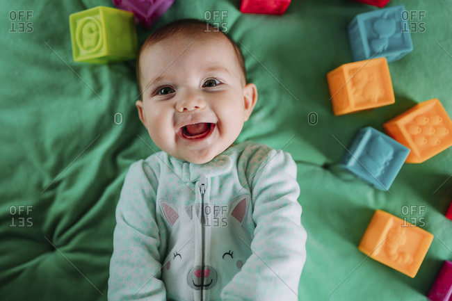 Portrait of happy baby girl lying on green mat among with rubber toys