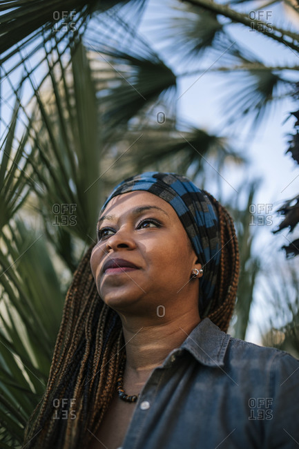 Portrait of woman with braids next to a palm tree