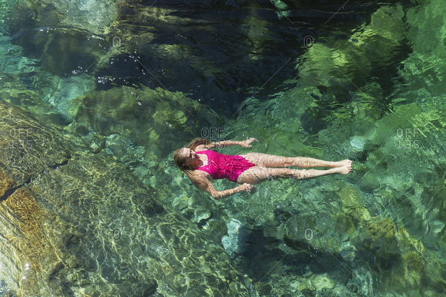 Woman swimming in refreshing Verszasca river