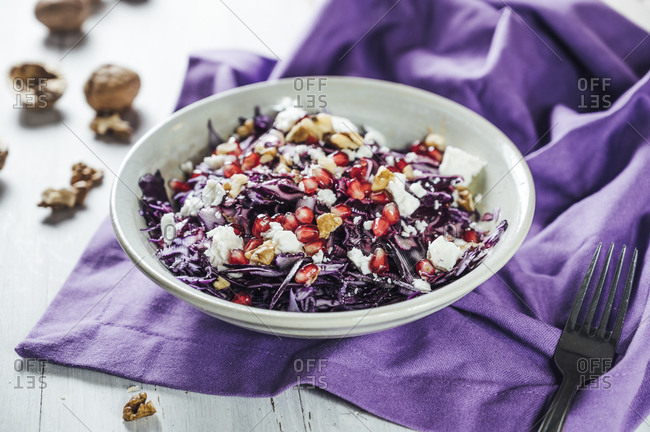Bowl of red cabbage salad with pomegranate seeds- walnuts and goat cheese