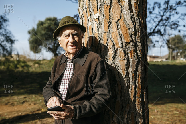 Old man using smartphone- leaning on tree trunk