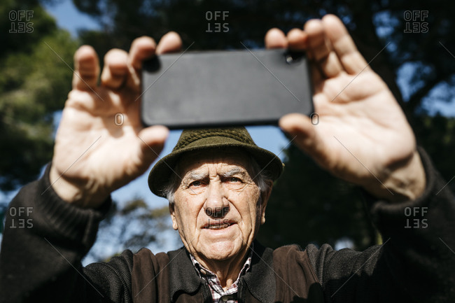 Old man taking pictures with his smartphone