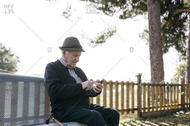 Old man with- sitting on bench- using smartphone