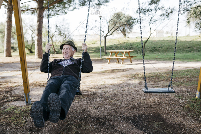 Old man swinging on playground in park