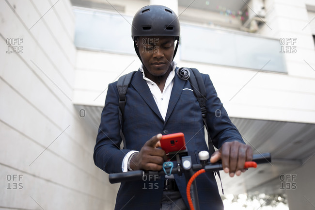 Portrait of businessman with push scooter looking at cell phone