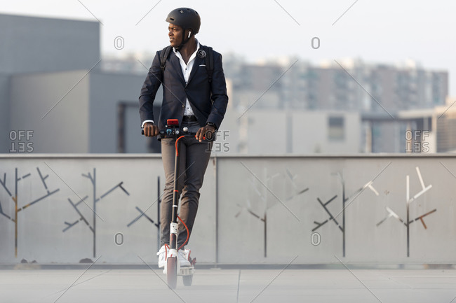 Businessman with backpack and cycling helmet riding push scooter in the evening