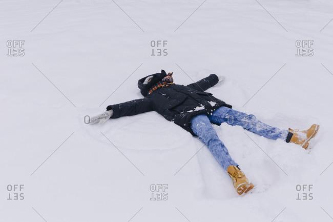 Woman lying on snow making snow angel
