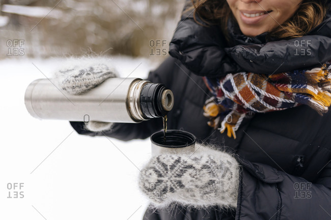 Crop view of woman pouring tea into thermo mug in winter