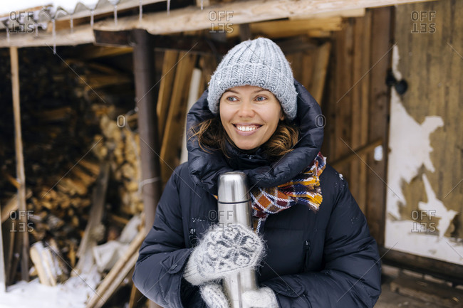 Portrait of happy woman with thermo flask in winter