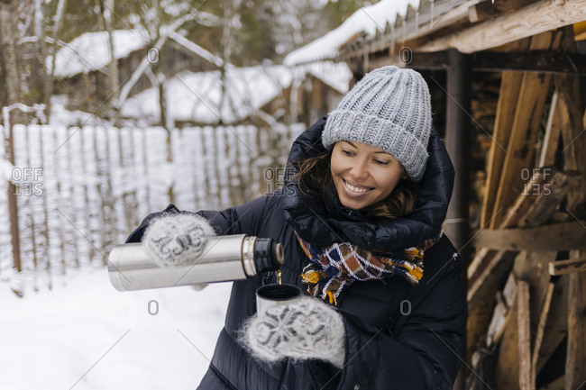 Portrait of happy woman using thermo flask in winter