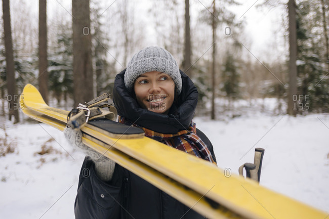 Portrait of smiling woman with skis in winter forest