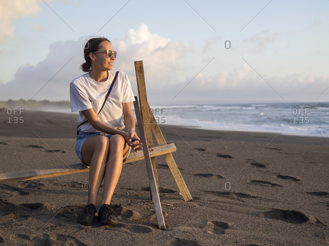 Woman sitting on rack on the beach at evening twilight- Kedungu beach- Bali- Indonesia