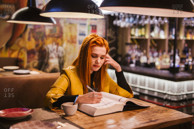 Portrait of redheaded young woman at table in a pub writing in a book