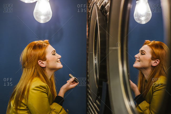 Smiling redheaded young woman looking at her mirror image applying lipstick