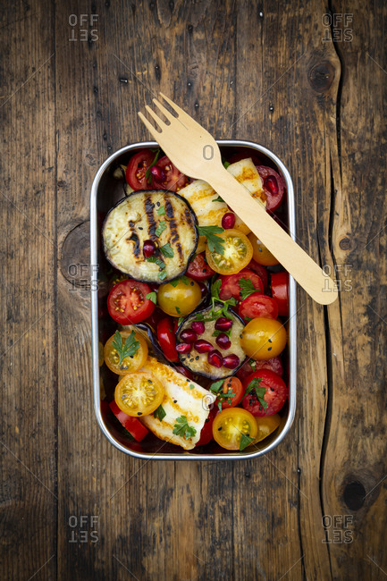 Lunch box with tomato salad with grilled vegetables and halloumi cheese- pomegranate seeds- sumac- black sesame and parsley