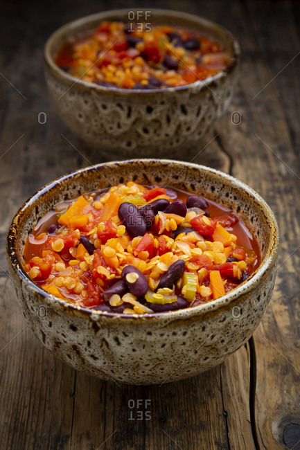 Bowls of vegan chili with red lentils- celery sticks- kidney beans- tomatoes and carrots