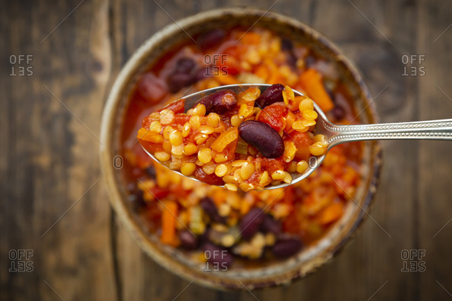 Spoon of vegan chili with red lentils- celery sticks- kidney beans- tomatoes and carrots