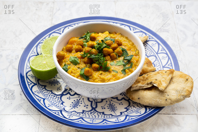 Vegan lentil curry with red lentils- sweet potatoes- spinach- roasted turmeric- chickpeas- with lime juice and coriander and naan bread