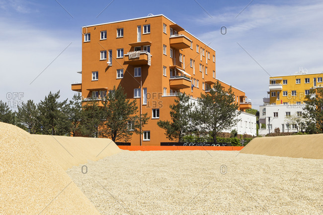 Germany- Bavaria- Munich- Sandy playground in front of orange painted residential building