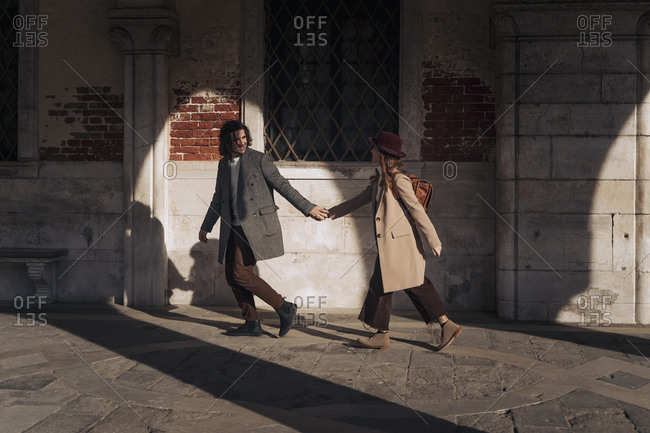 Young couple walking hand in hand in the city of Venice- Italy