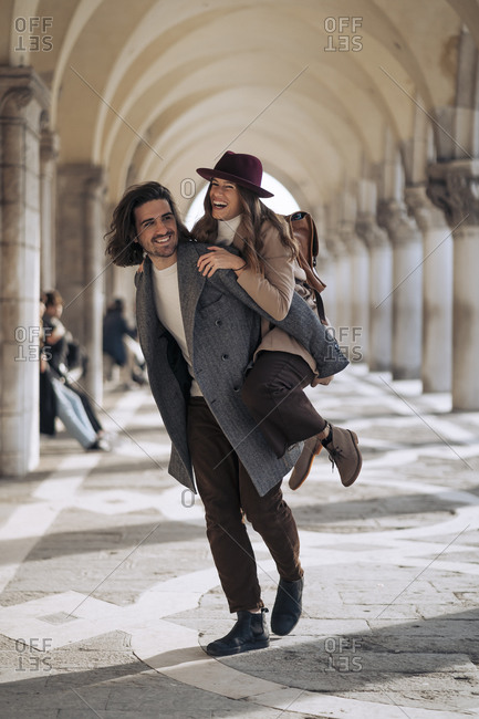 Young man giving his girlfriend a piggyback ride in the city of Venice- Italy