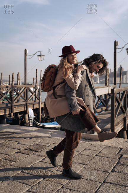 Young man giving his girlfriend a piggyback ride at the waterfront in Venice- Italy