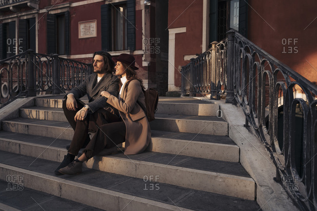 Young couple sitting on a bridge in the city of Venice- Italy