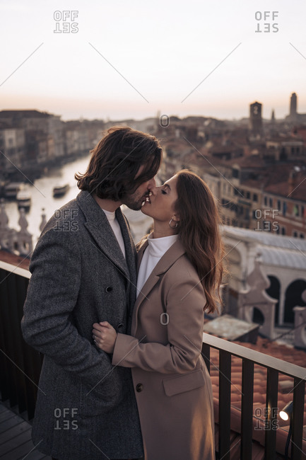 Affectionate young couple kissing on a balcony above the city of Venice- Italy