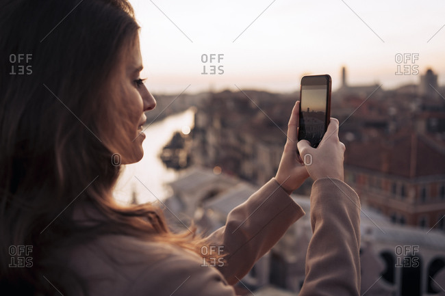 Young woman taking cell phone picture on a balcony above the city of Venice- Italy