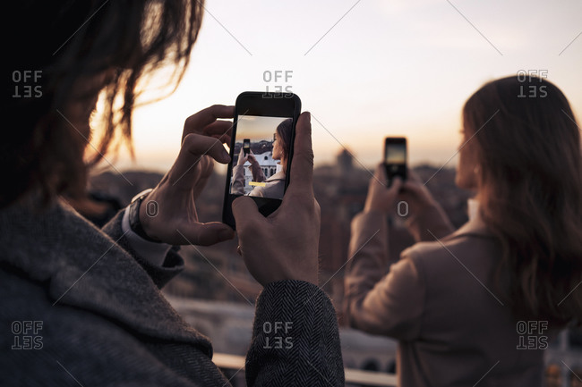 Young couple taking cell phone pictures on a balcony above the city of Venice- Italy