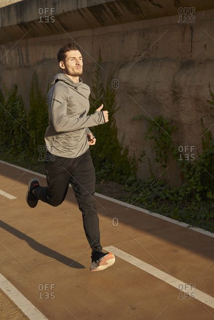 Man running on a road in sunlight