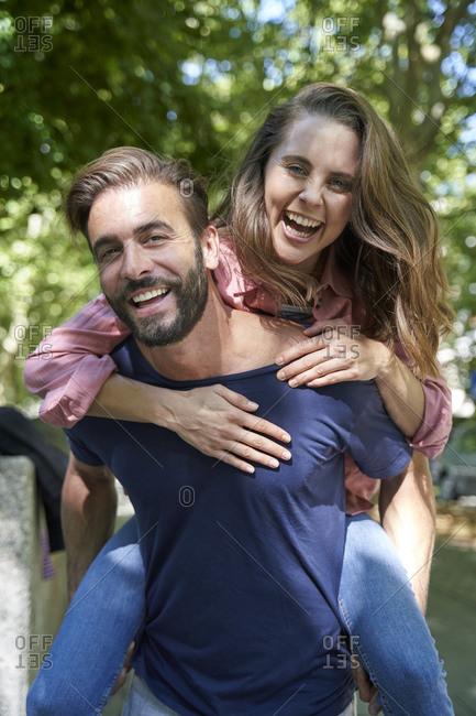 Portrait of happy man carrying woman piggyback