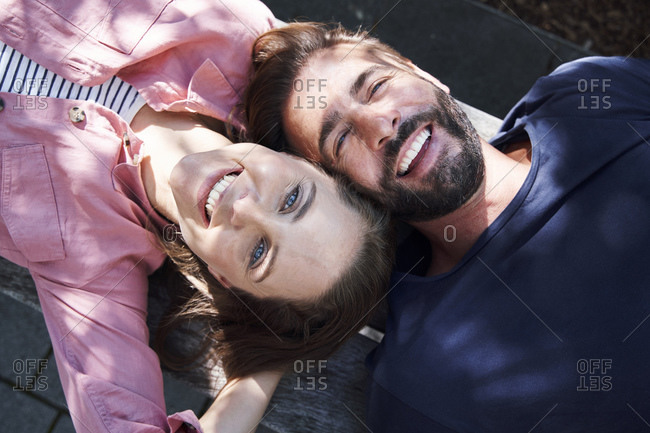 Portrait of happy couple lying on a bench head to head
