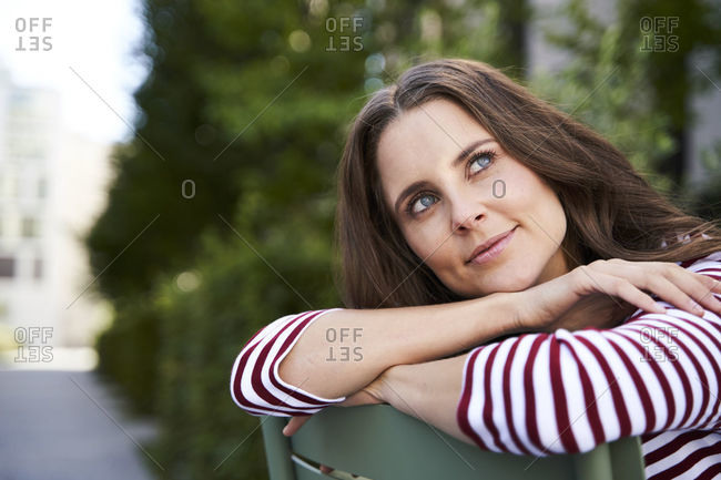 Portrait of daydreaming brunette woman sitting on a chair in the city