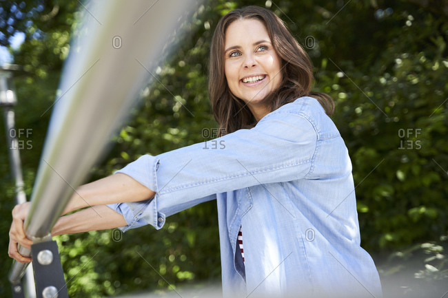 Portrait of happy brunette woman leaning on railing outdoors