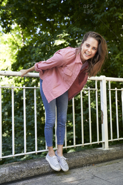 Portrait of happy brunette woman holding railing outdoors
