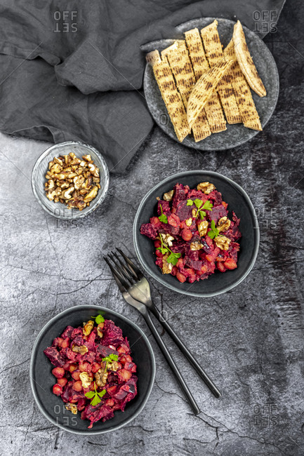 Pita bread and plates of beetroot salad with chick-peas- roasted walnuts and parsley