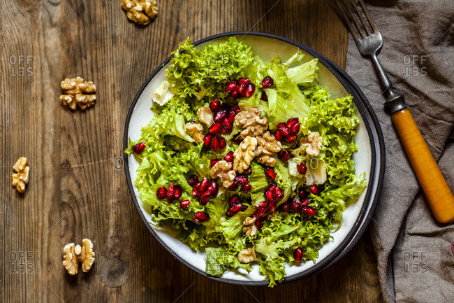 Bowl of green salad with walnuts and pomegranate seed