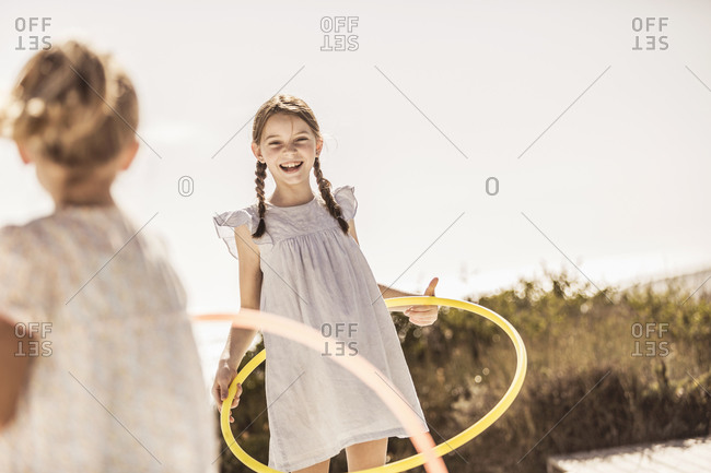 Two happy girls playing with hoola hoop on terrace of a beach house