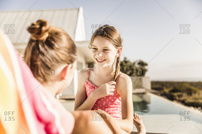 Portrait of happy girl with her mother at the poolside