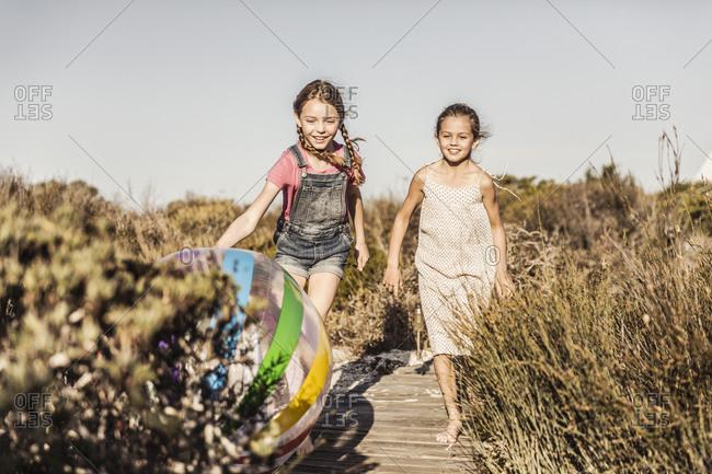 Two happy girls running on boardwalk in dunes