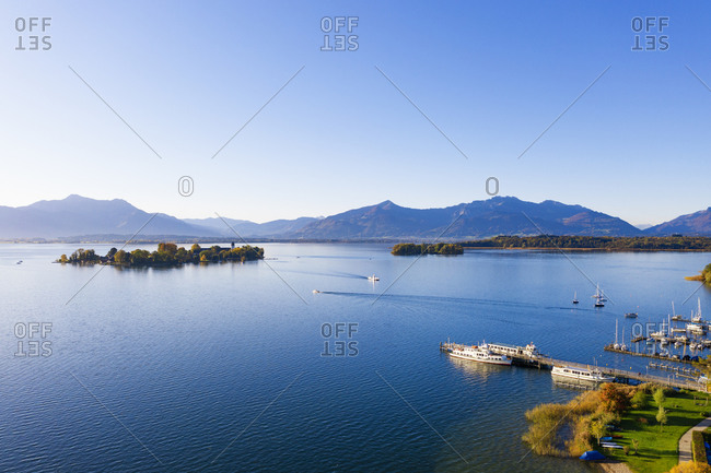 Germany- Bavaria- Gstadt am Chiemsee- Clear sky over blue Chiemsee lake with mountains in background