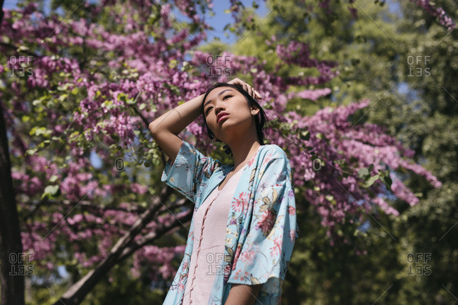 Beautiful young woman with blooming cherry tree in a public garden in spring