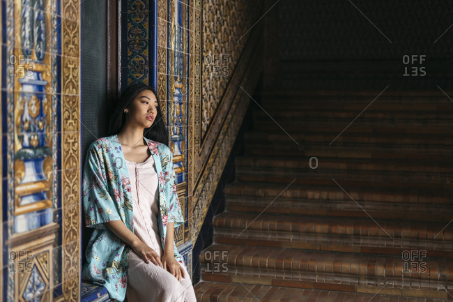 Portrait of beautiful young woman wearing a kimono sitting on a ledge