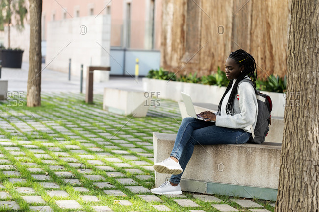Female student using laptop on a bench