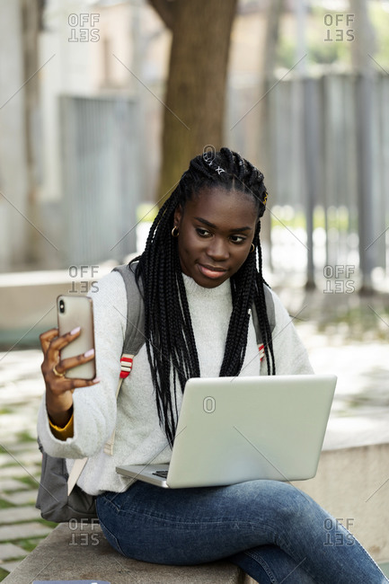 Female student using laptop and cell phone on a bench