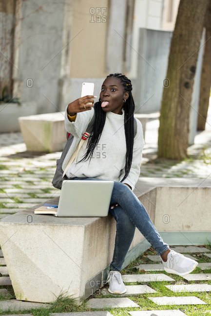 Playful female student taking a selfie on a bench